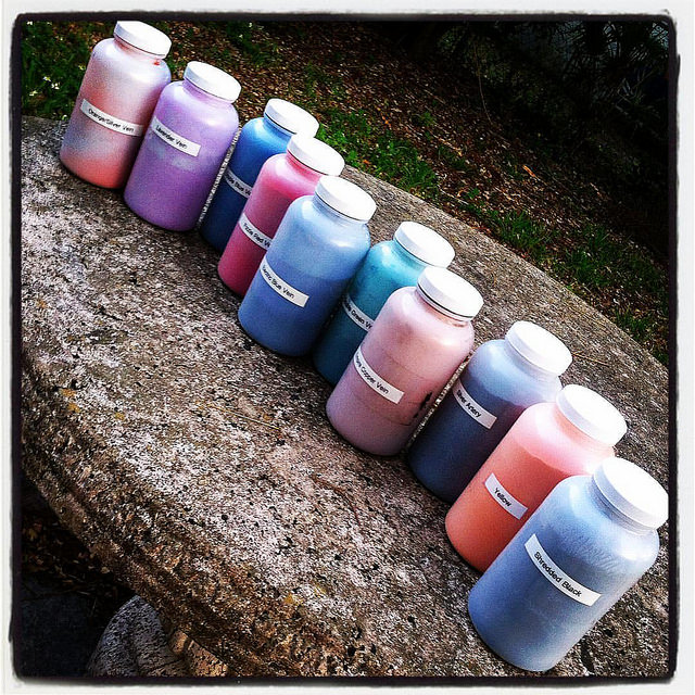 Image: 7 jars of powder coat pigment in red, purple, blue, and orange
